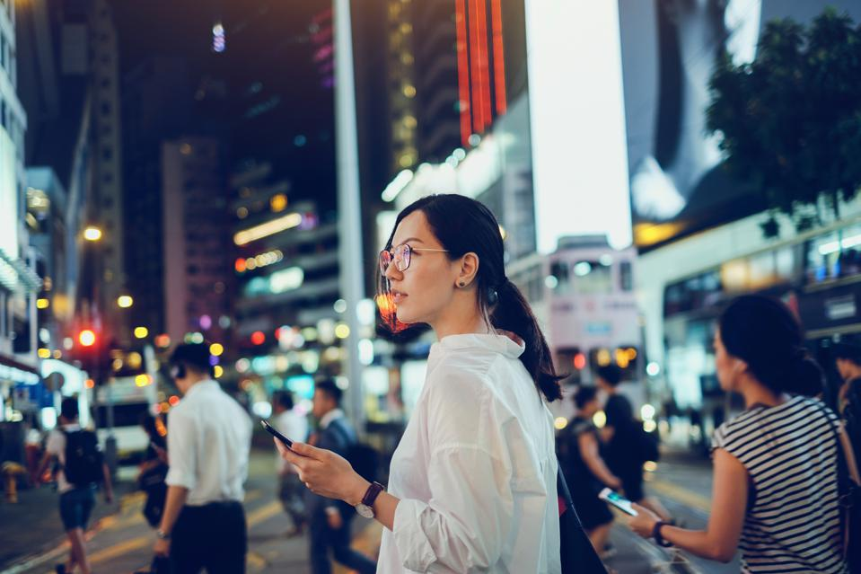 Beautiful Asian woman using mobile phone while crossing road in busy downtown city street at night