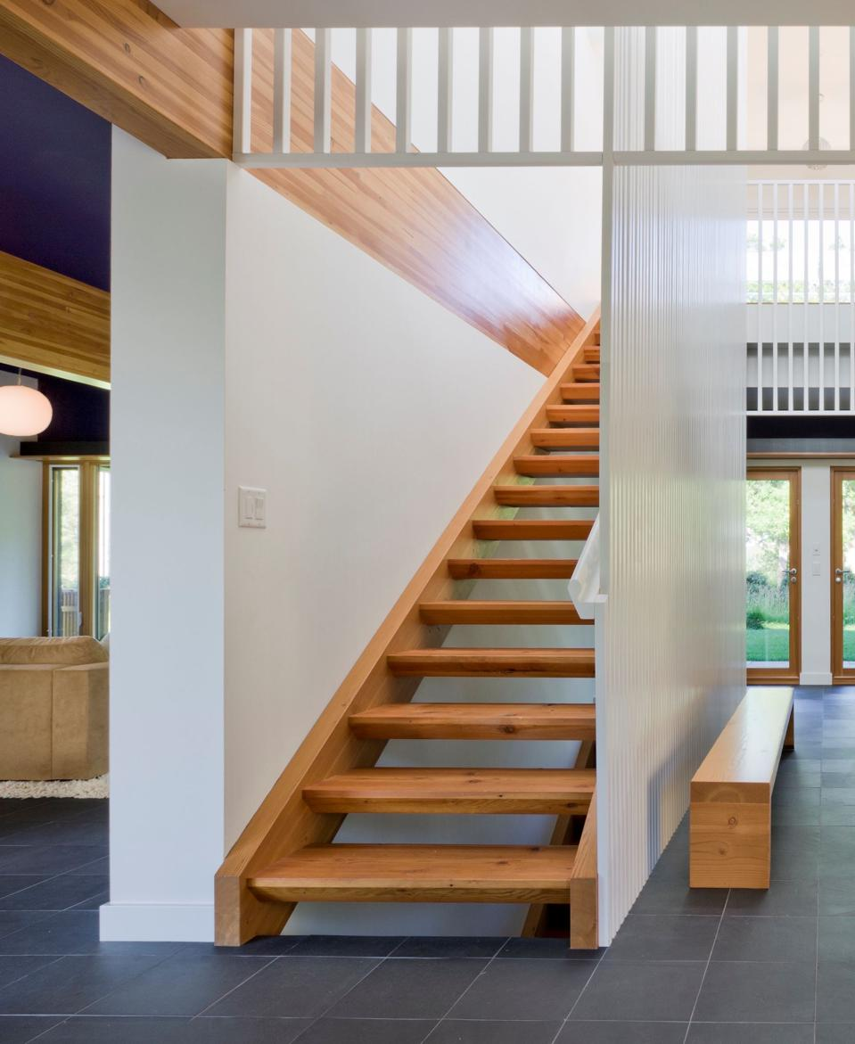Reclaimed fir stairs connect the lower and upper floor. A translucent wall panel and lots of windows flood the home with natural light.