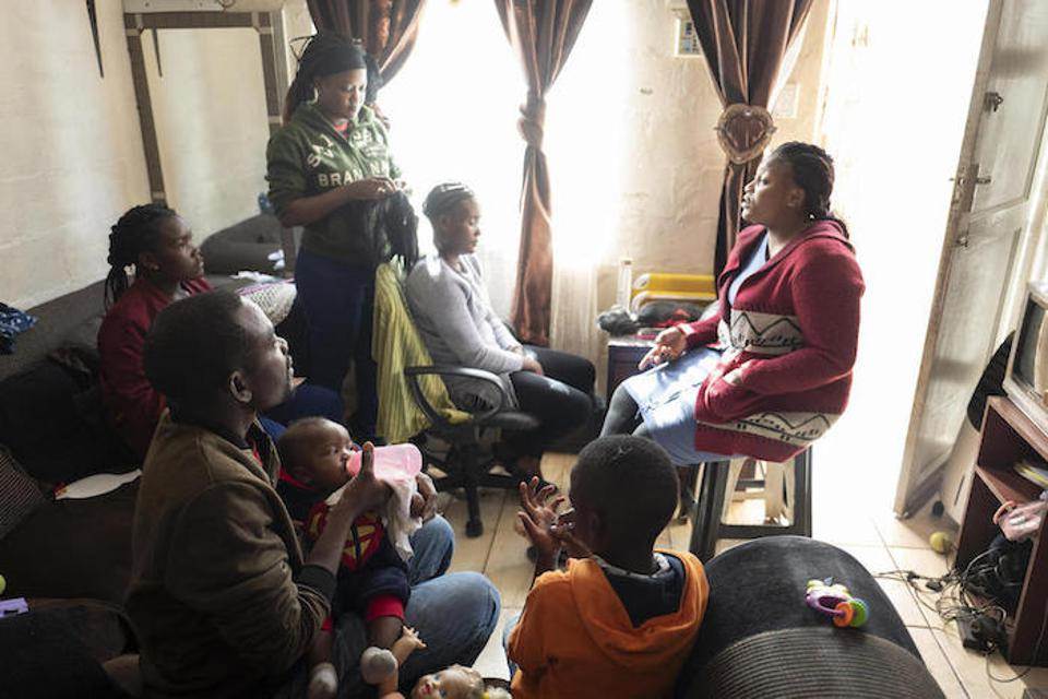 Congolese refugees Dieu-Merci Matala, 44, and his wife, Bibiche (standing) are raising their family in Cape Town, South Africa with support from UNICEF and Sonke Gender Justice.