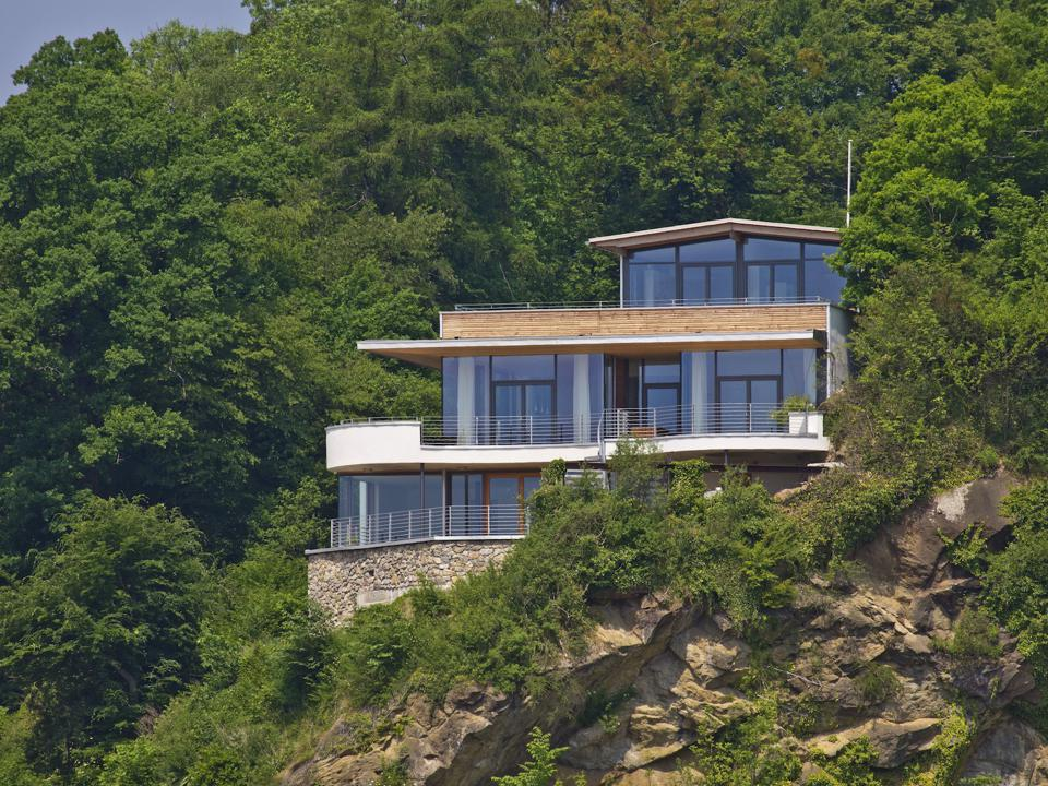 The house can be seen nestled into the cliff. The house was manufactured and built by Baufritz and designed by architect Daniel Wagner.