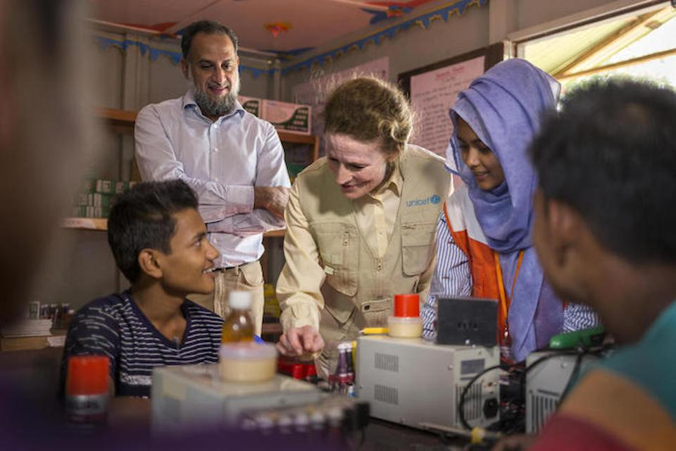 UNICEF Executive Director Henrietta Fore (center) and the United Nations Secretary General's Humanitarian Envoy, Ahmed Al Meraikhi (standing) visited with young people learning to repair cell phones in Tenkali refugee camp, Bangladesh in February 2019.