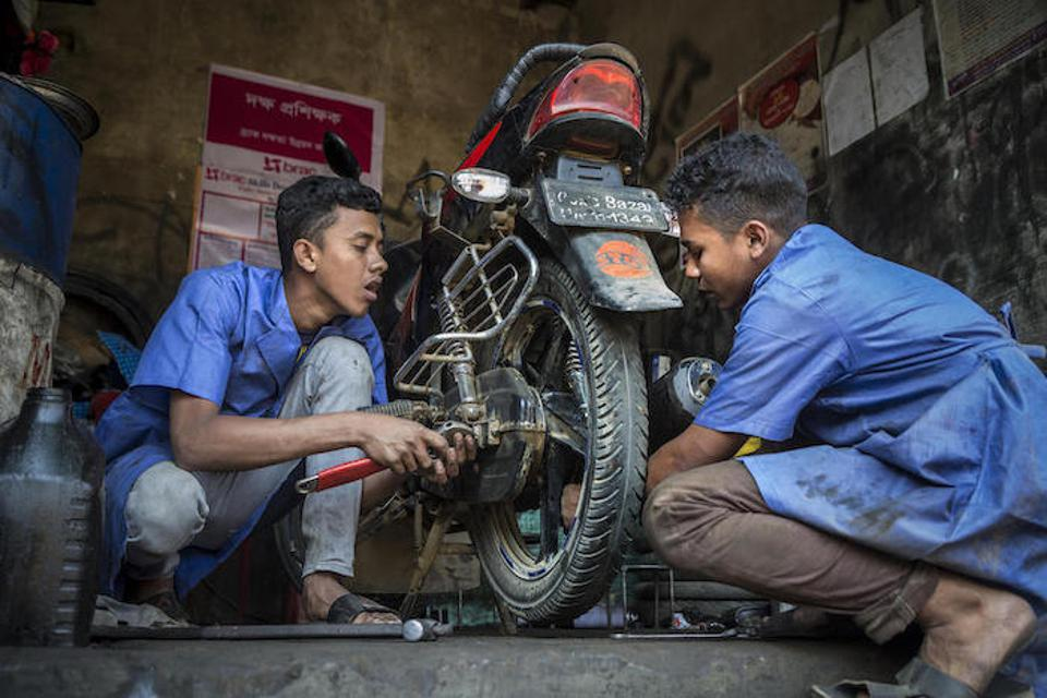 Mohammed Forhad (above left) and Biplob Barca, both 18 years old, work on a motorbike in a garage in Court Bazar.