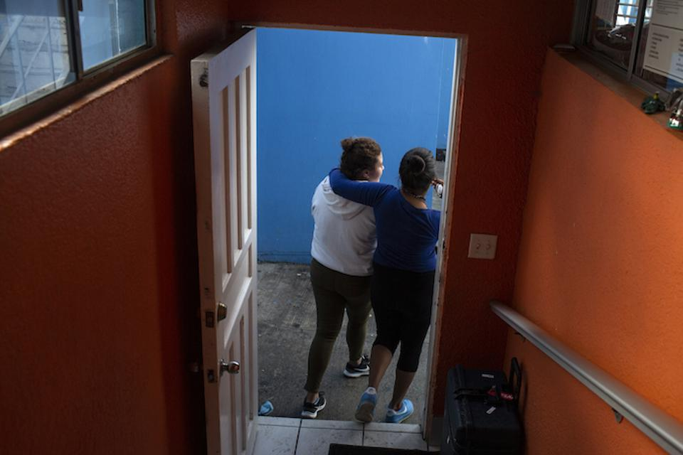 Two teens from Central America walk out of an open-door shelter for unaccompanied migrant adolescents in Tijuana, Mexico.