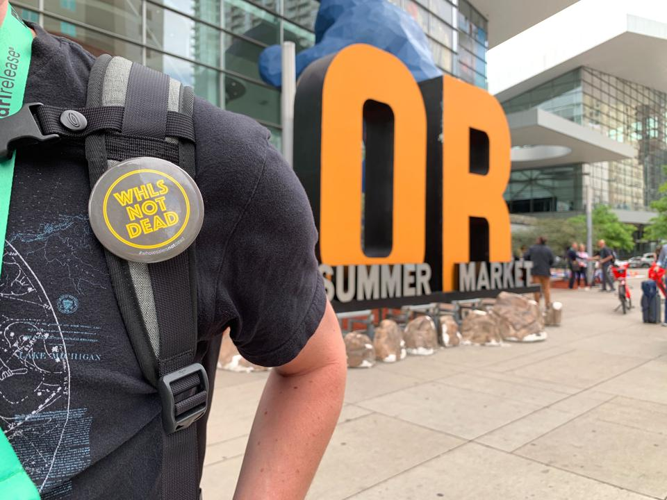 A closeup photo of the Wholesale is Not Dead campaign button on an attendee at the Outdoor Retailer trade show in Denver from June 17-20.