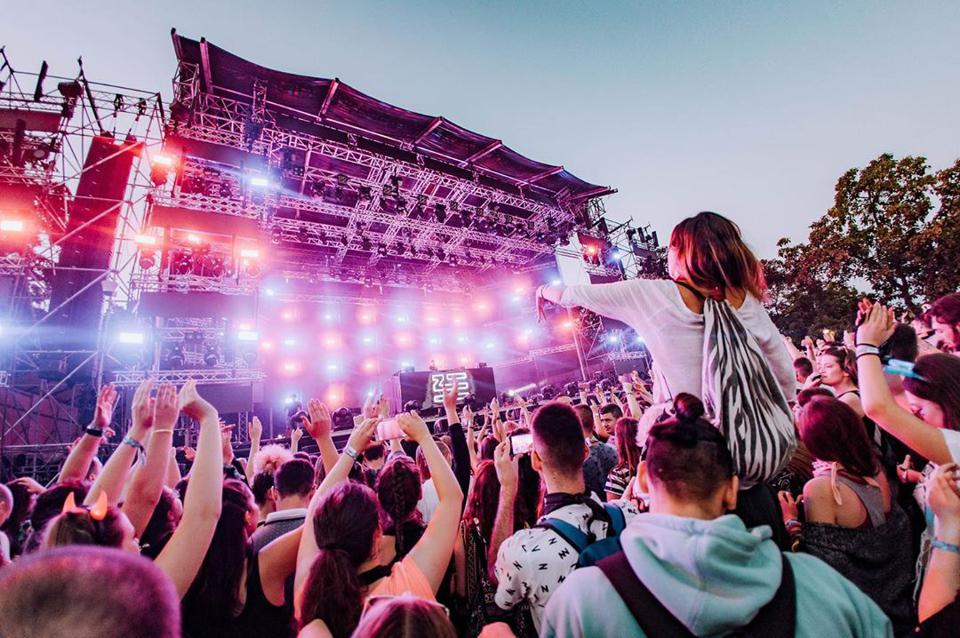 A bright music festival stage with a large, energetic crowd.
