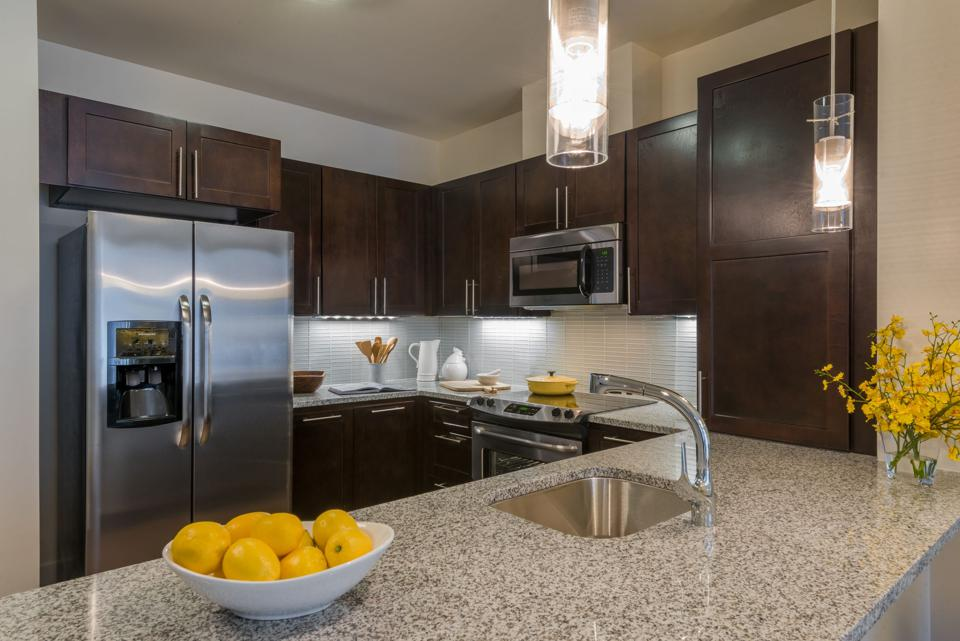 Kitchen counter, prep sink on island, bowl of lemons, stainless appliances.