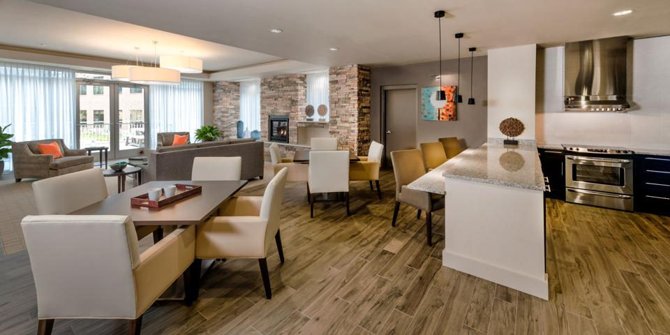 Open dining room with tables and an island in a kitchen lounge area used by residents and guests.