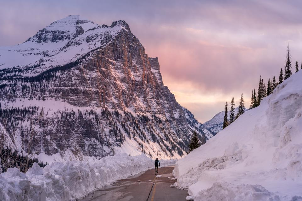 An early-season biker taking advantage of a blissfully quiet Going to the Sun Road before it opens to cars.