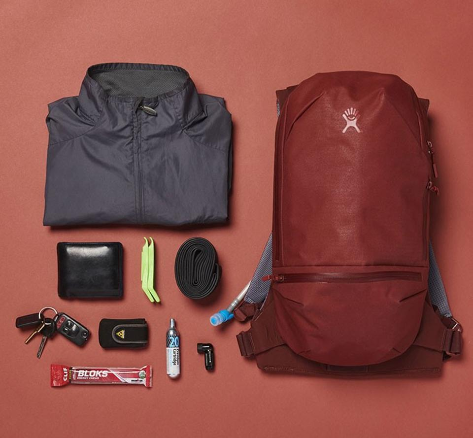 Red backpack with accessories laying beside