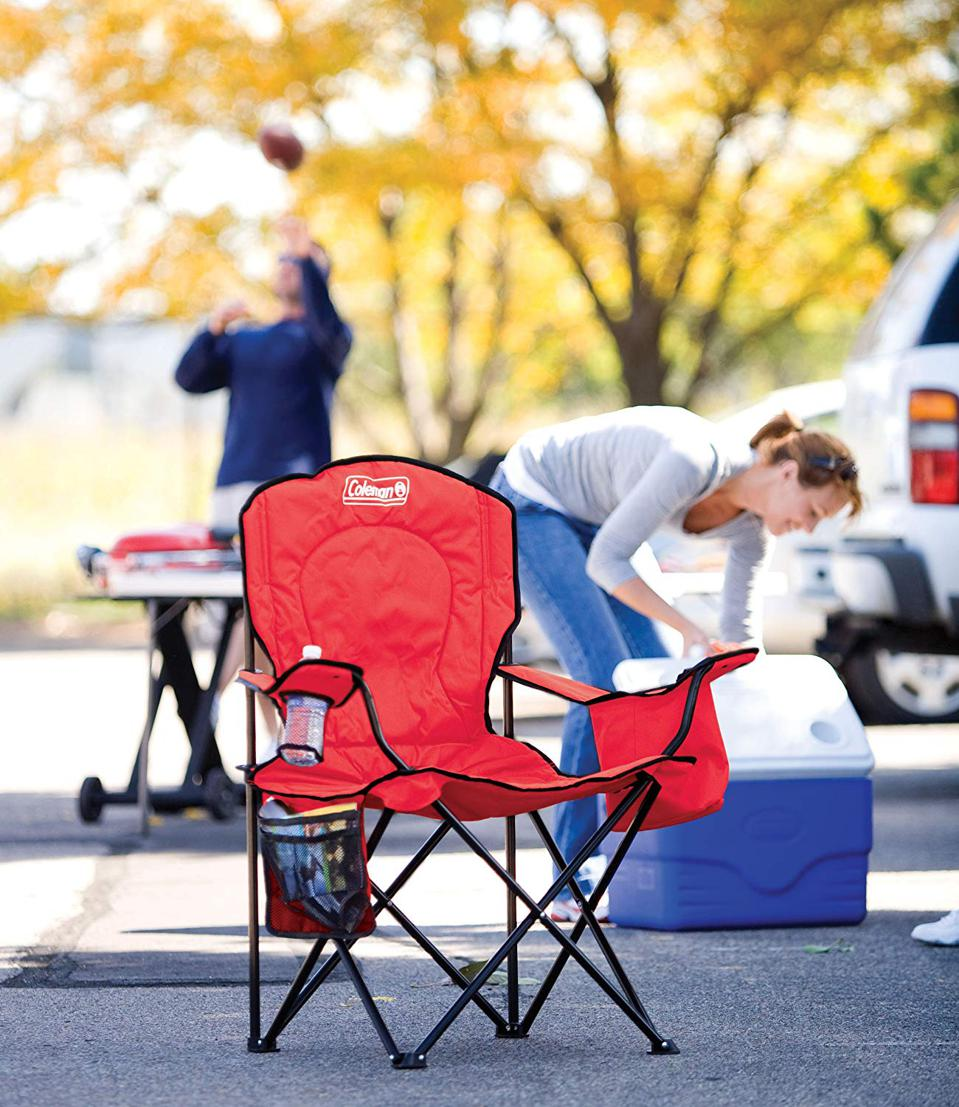 Red camping chair with woman getting into cooler in the background