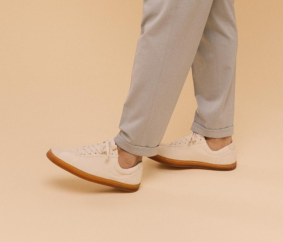 Man with roller up pants wearing off white shoes
