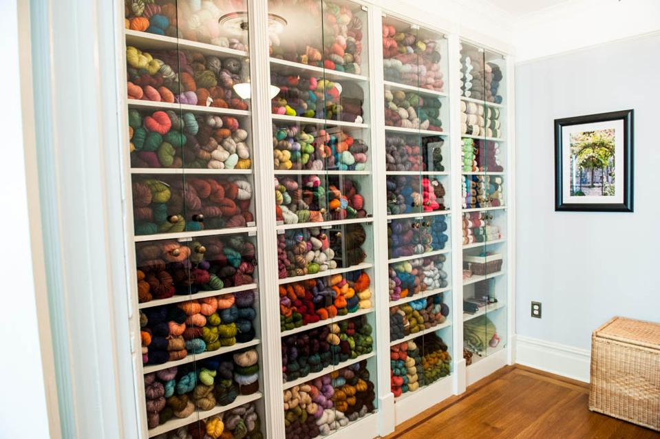 Shelves behind glass filled with colorful yarn.
