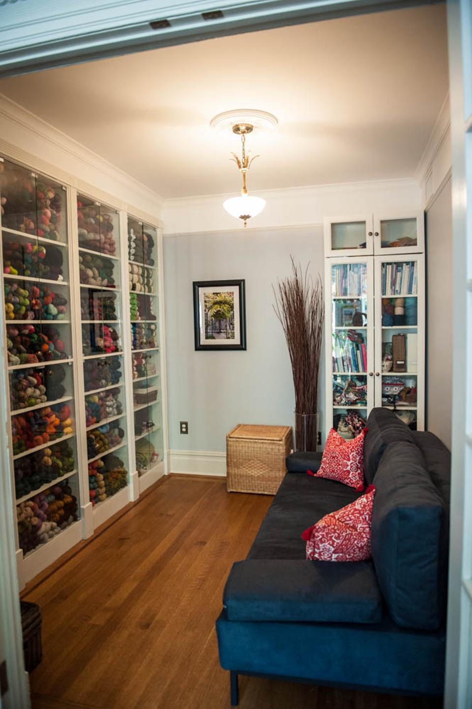 A room with shelves of yarn and a blue sofa.