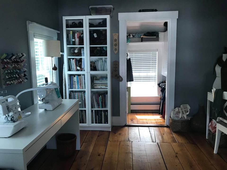 A craft room with a sewing table and gray walls.