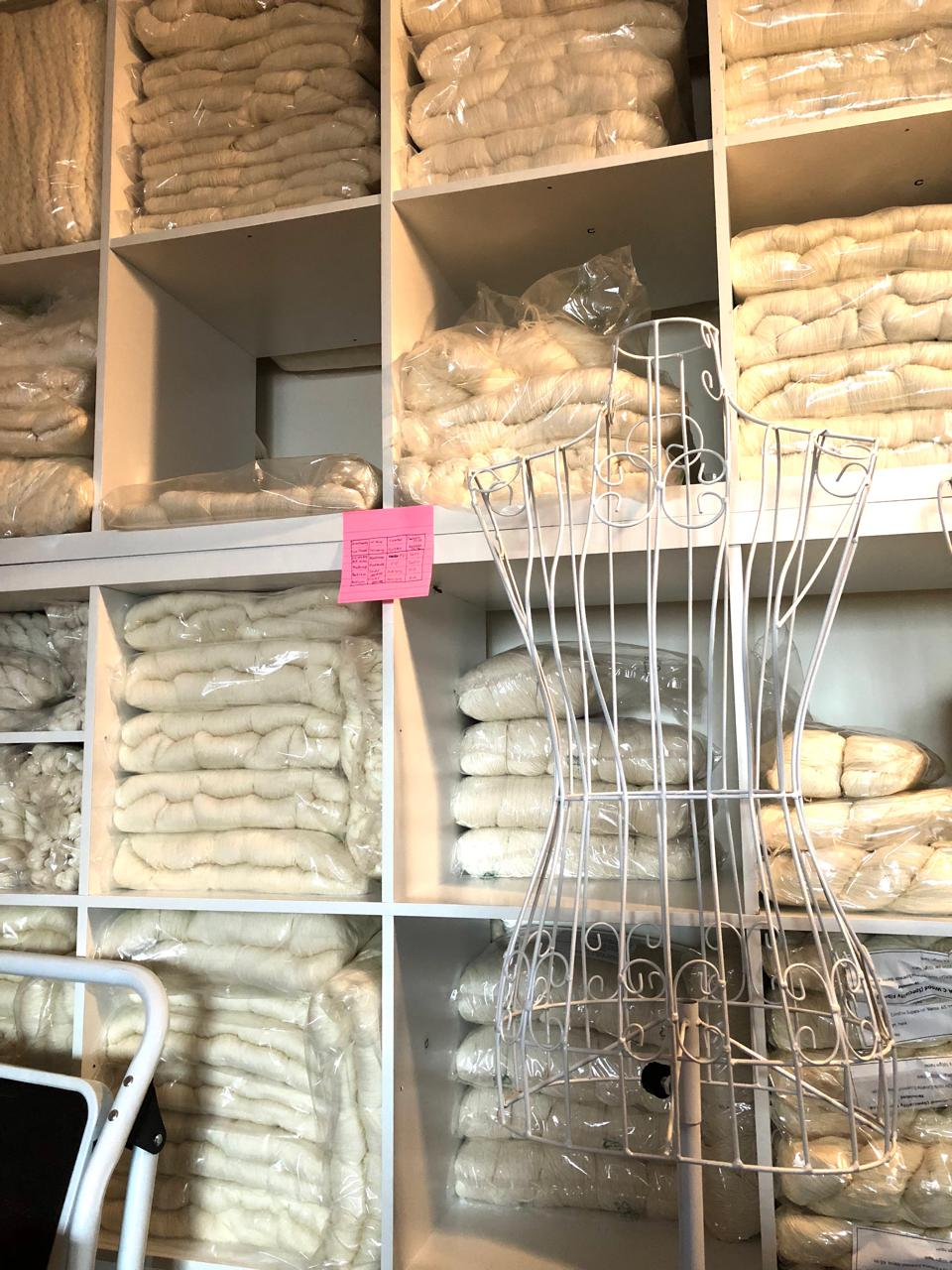 Shelves of un-dyed yarn and a metal dress form.