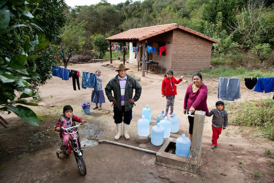 A family in Bolivia uses a community tap to access safe water