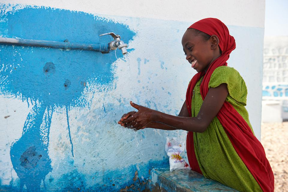 A girl in Djibouti washes with soap and tap water outside a UNICEF-supported school in Djibouti