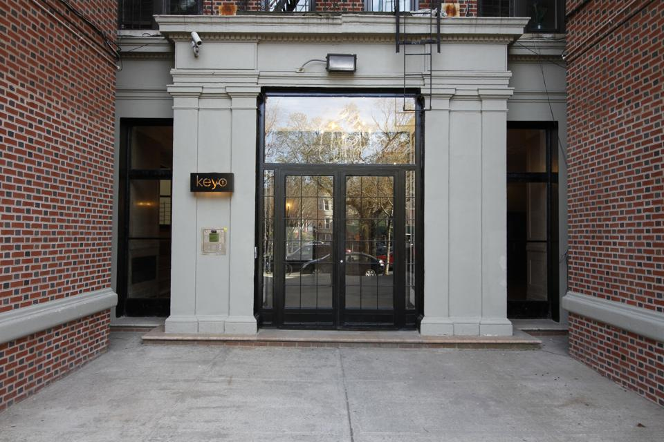 The entrance of an apartment building with a Keyo sign.