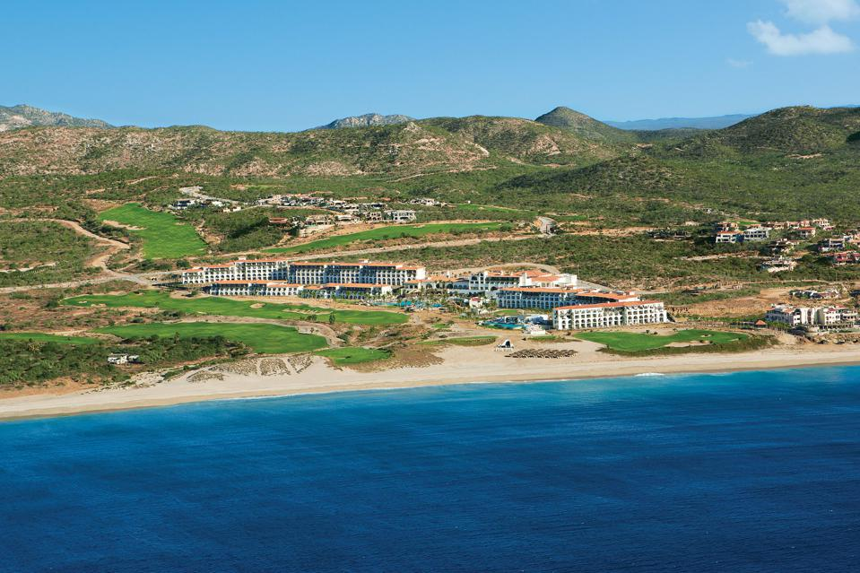 Ocean and beach with hotel and golf course in the background