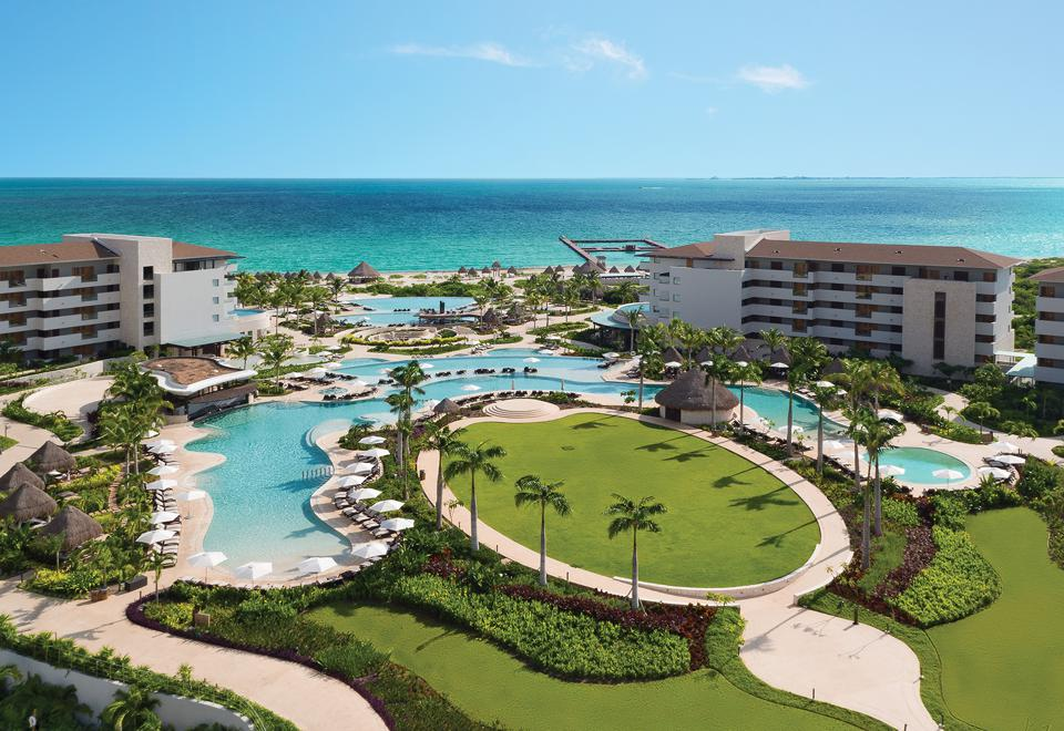 Resort with pools and golf course and the ocean in the background