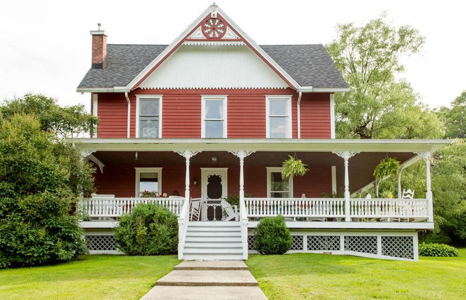 Red two-story farmhouse style home with a wrap around porch.