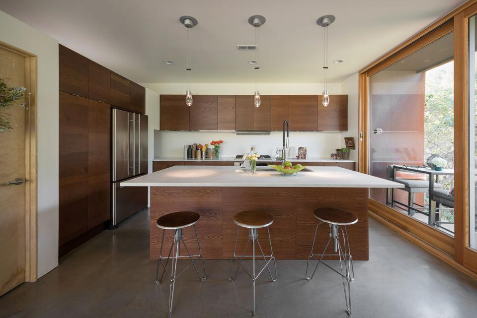 modern kitchen with warm wood cabinets and large white island.