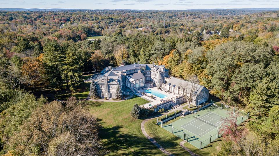 A drone view of an estate with a tennis court.