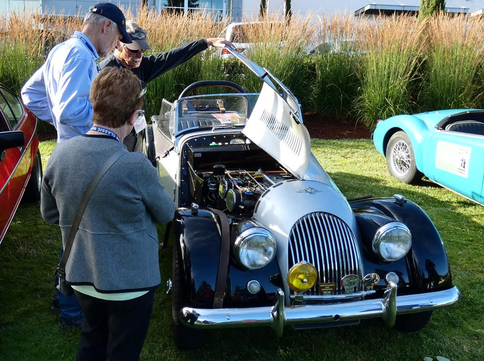 The owner of a vintage Morgan pops open the bonnet for a curious onlooker.