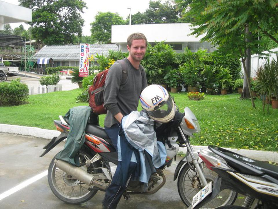 A man with a backpack sits on a dirt bike.