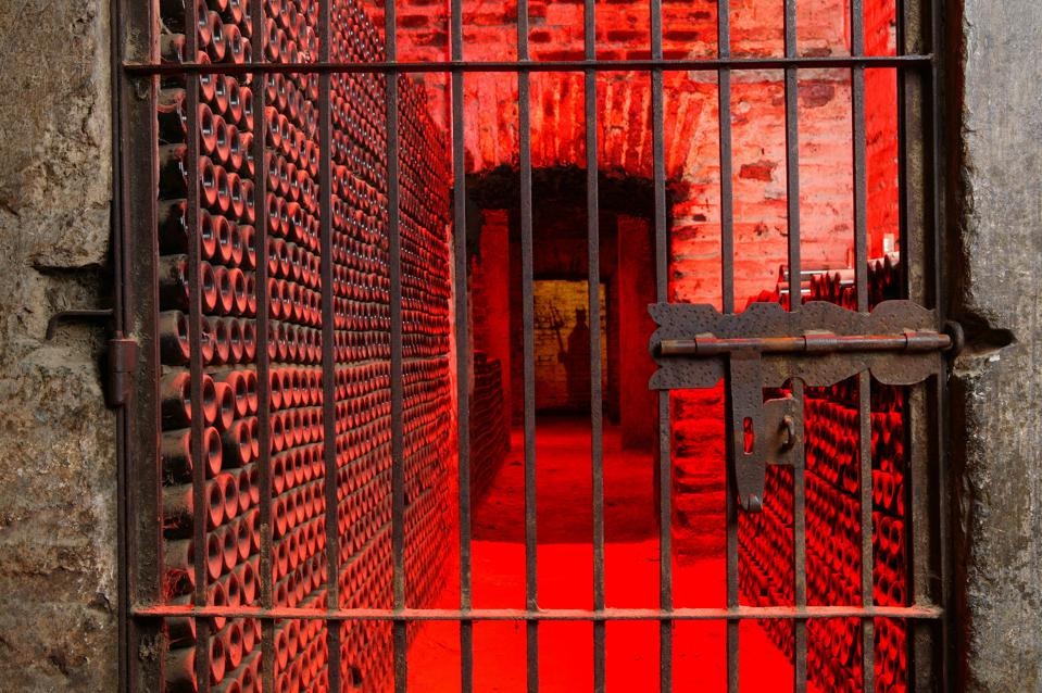 A photo of a wine cellar, lit with red lights, and a shadow of the devil on the far wall.