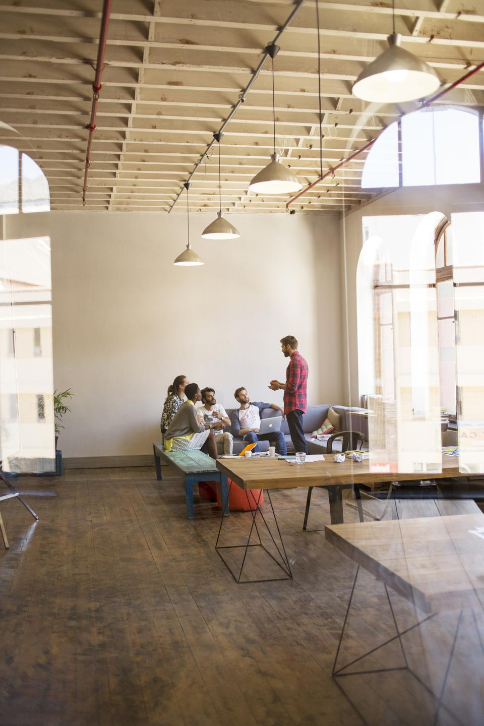 Creative businessman leading meeting in open office