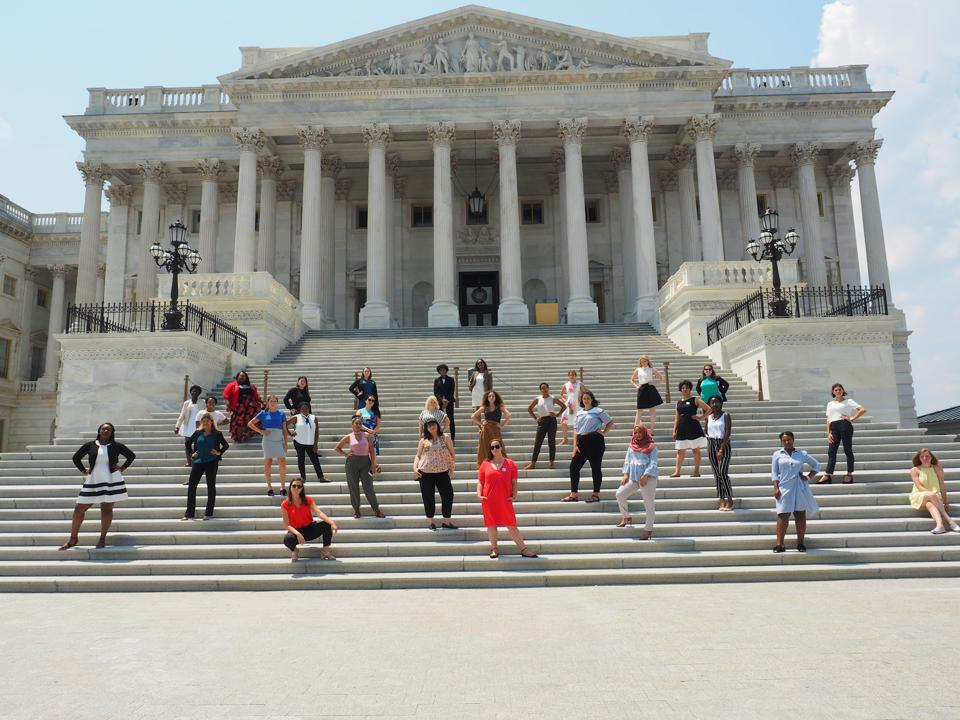 A group of women strike a powerful pose on the steps of the U.S. Capitol.
