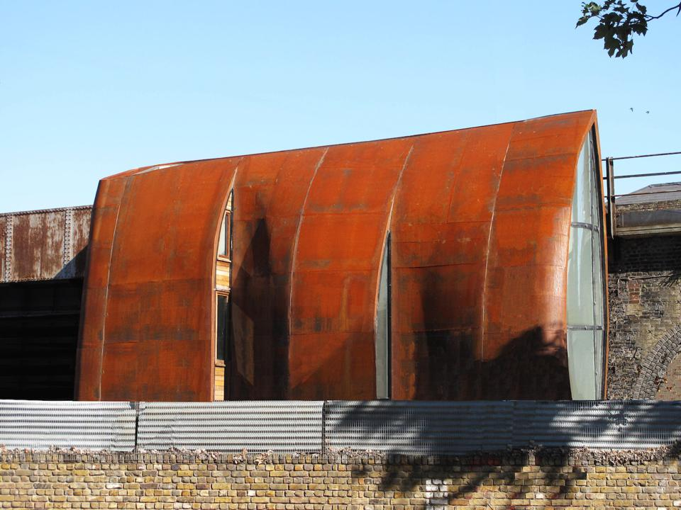The building shell is made from weathered steel that fits in with the industrial nature of the area.