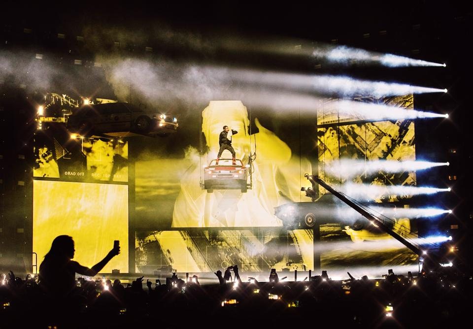 ASAP Rocky on stage, standing on a suspended car and surrounded by yellow images.