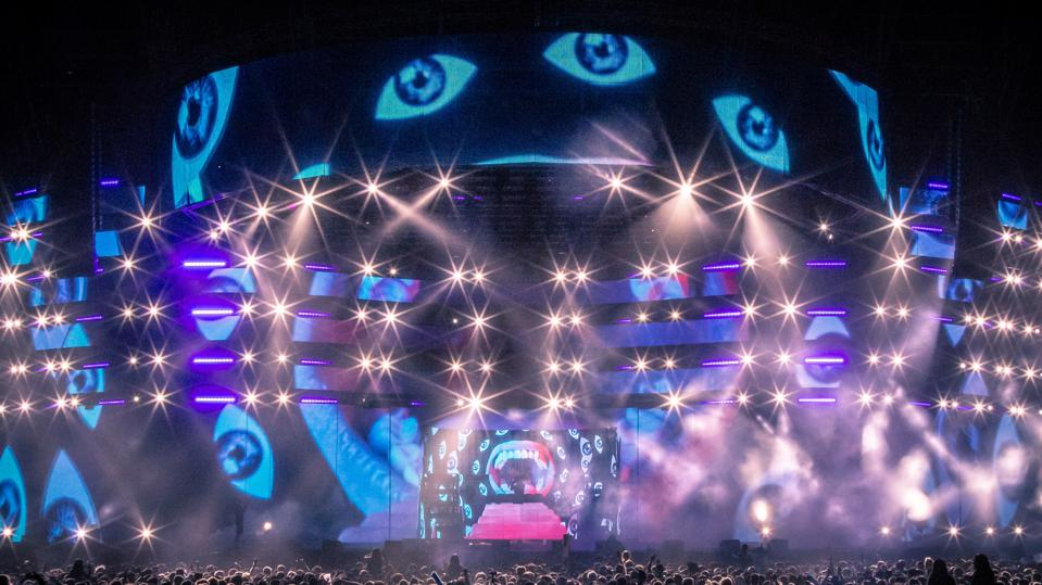 Diplo on stage at Coachella surrounded by images of eyes.