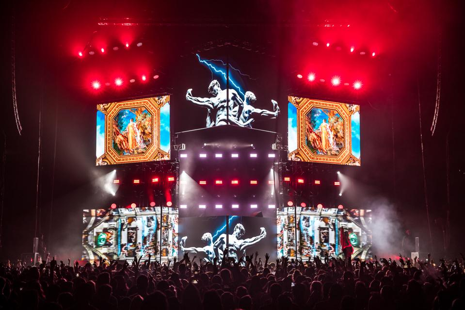 Russ on stage surrounded by visuals resembling classical artwork
