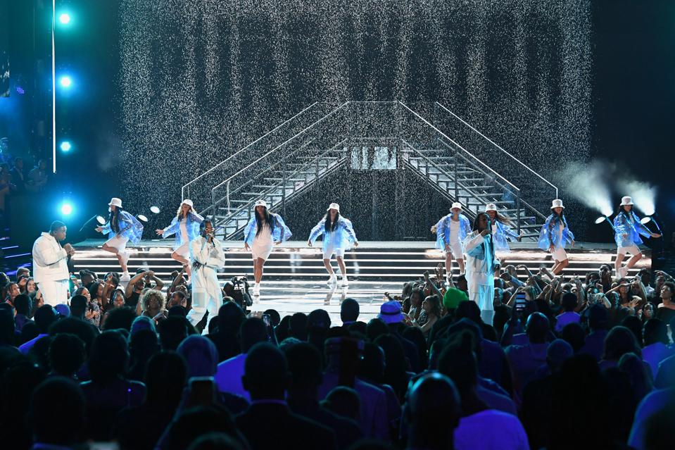 Mustard and Migos on stage with dancers and a waterfall spelling ″Pure Water″
