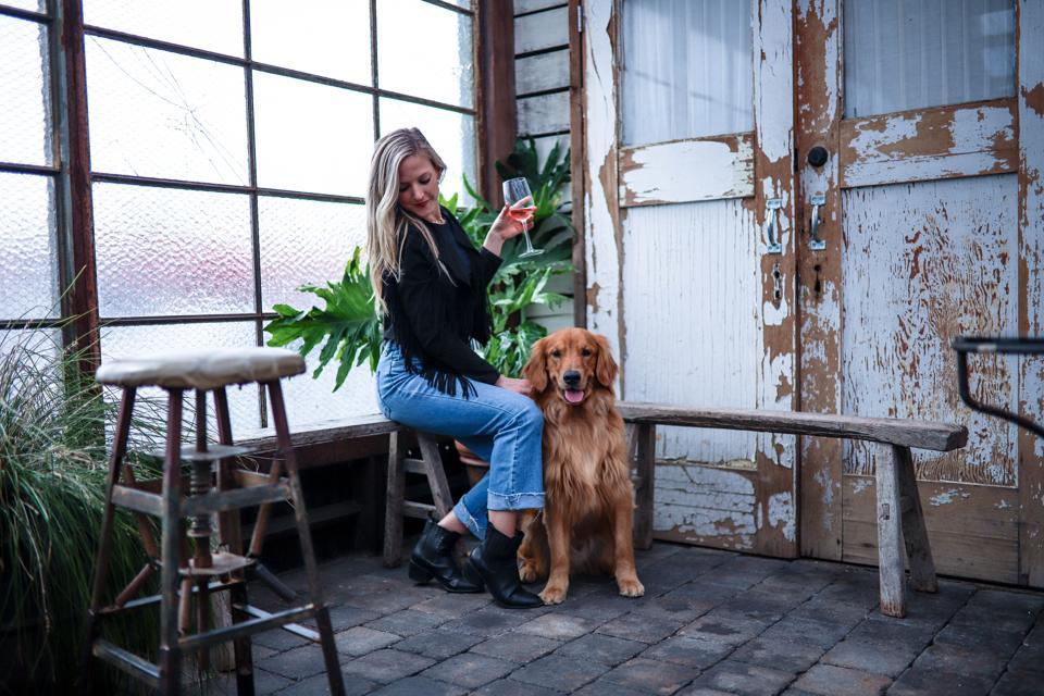 Woman enjoying wine with dog