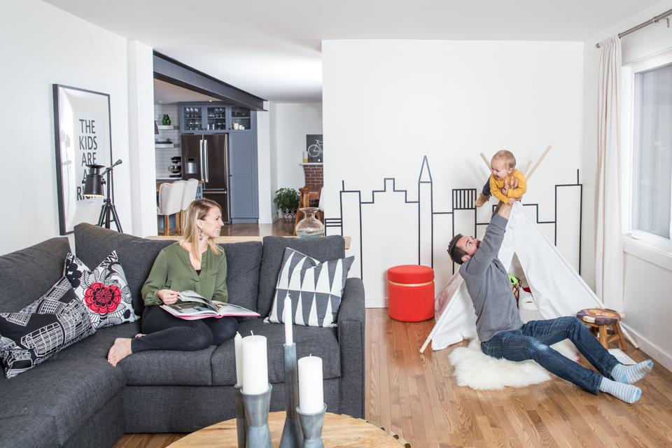 Mother, father and baby playing in their new living room.