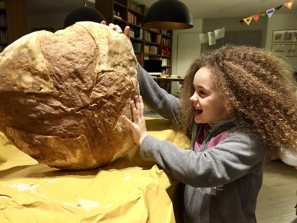 The couple's daughter, Lea, with a rustic, 5 kg (11-pound) Apulian loaf of bread