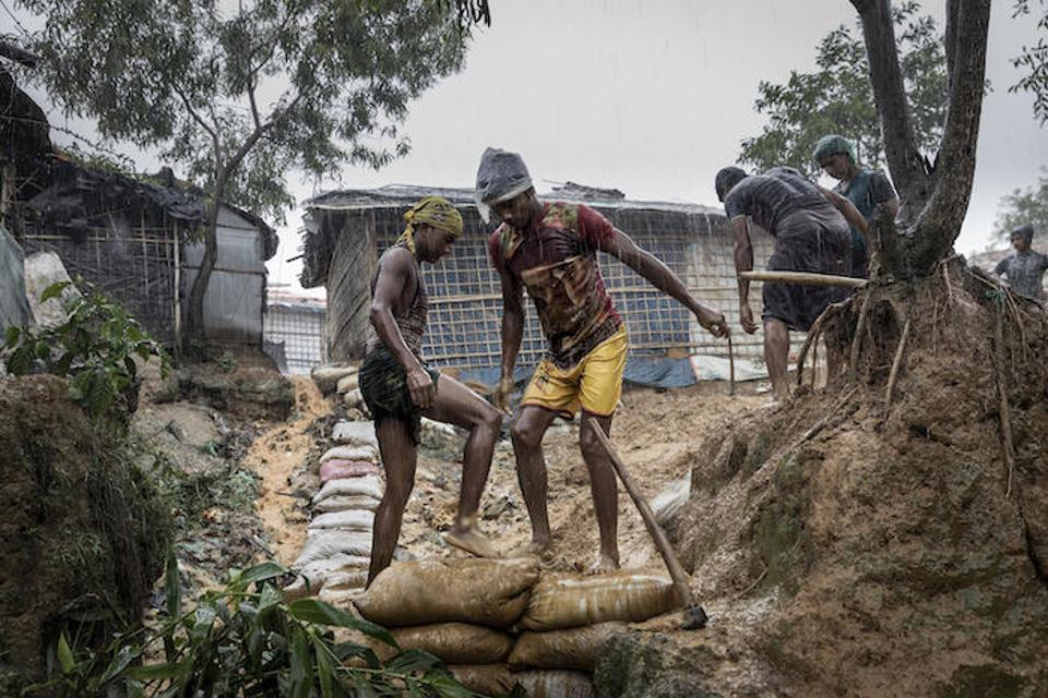 On July 6, 2019 in Bangladesh, two men reinforce a mountainside path in a flooded Rohingya camp in Cox's Bazar.