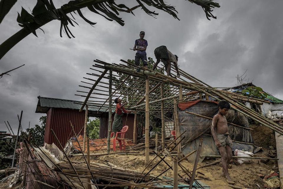 On July 7, 2019, men rebuild a house destroyed the night before by strong winds in Camp 18, part of the Kutapalong refugee camp in Cox's Bazar.