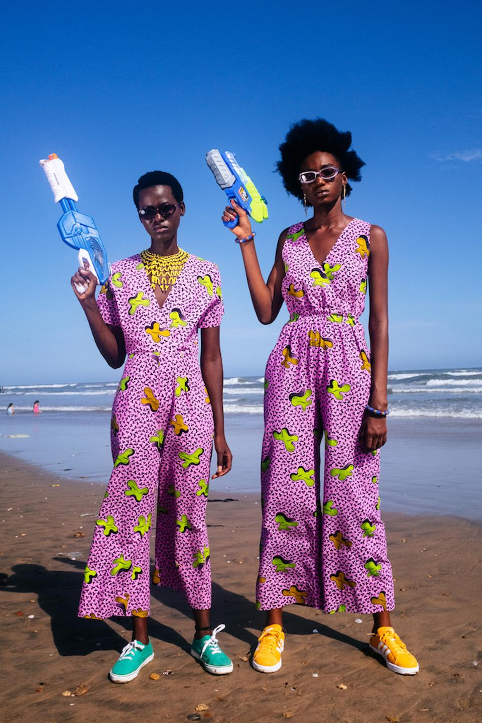 Two African models wearing matching pink-printed jumpsuits standing on a beach brandishing water guns.