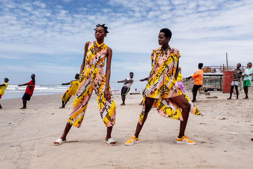 Two models wearing jumpsuits of the same fabric lean on a beach.