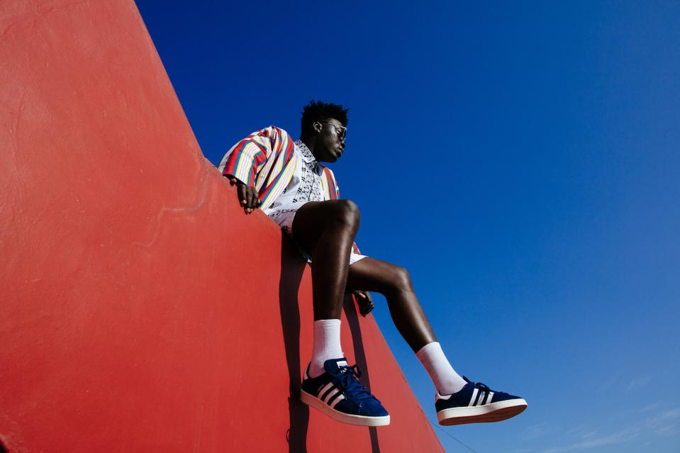 A male model sits on a red wall with a blue sky above.