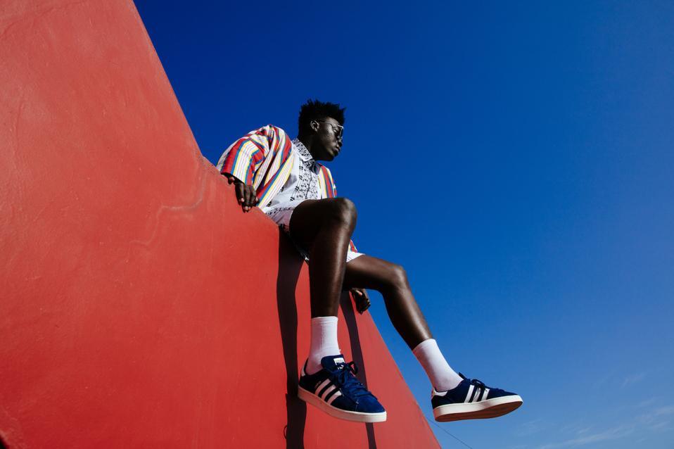 Un modelo masculino se sienta en una pared roja con un cielo azul arriba.
