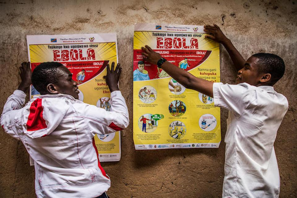 Students put up Ebola education posters on the walls of La Vérité school in Butembo, North Kivu, Democratic Republic of Congo on March 23, 2019.