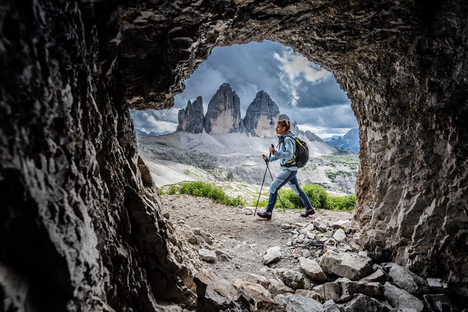 Woman hiking, seen through a circle in rock, in mountainous area.