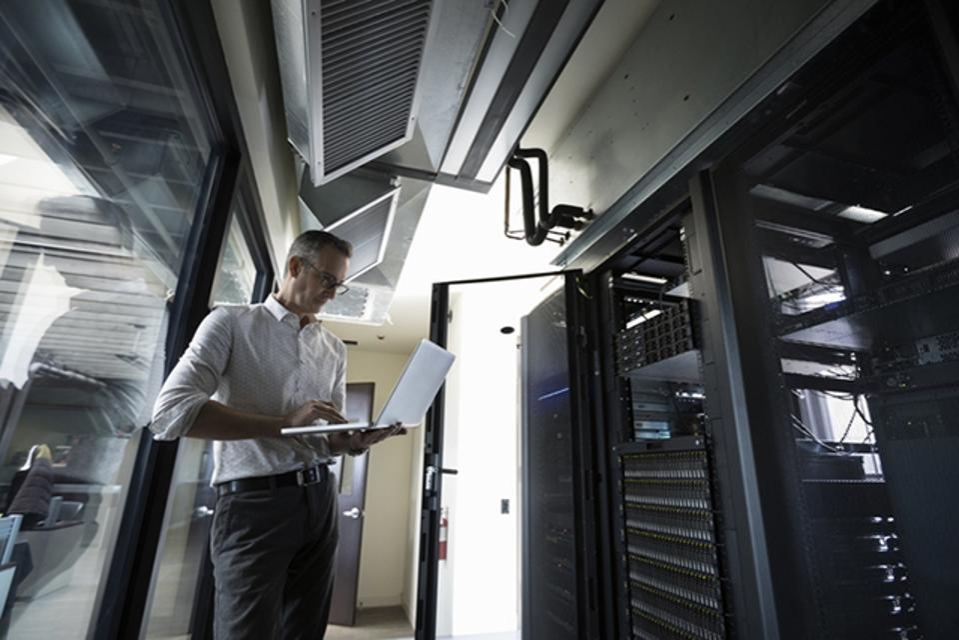 IT technician using laptop in server room