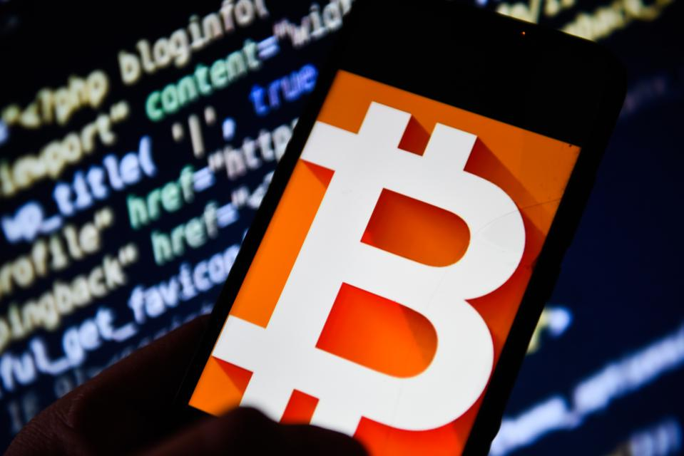 Bitcoin logo is seen on an android mobile phone...